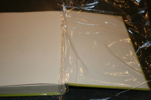 Flip to the back cover. Get a nice big piece of plastic wrap and line it up with the inside of the spine.